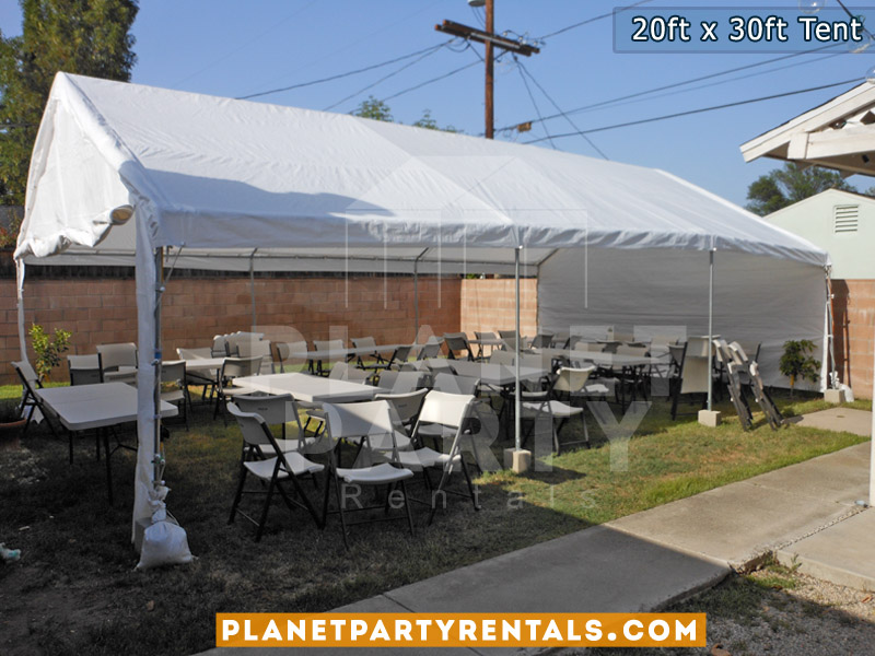 20x30 Tent setup on grass. Also pictured are rectangular tables and plastic chairs.